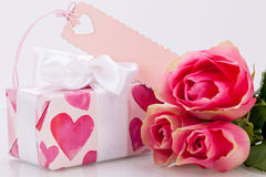 Gift box with an empty tag, next to three roses Royalty Free Stock Photo