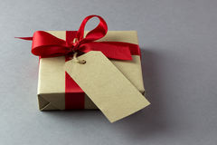 Gift box with empty tag. Rustic gift box with empty tag and red bow Stock Photography
