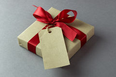 Gift box with empty tag. Rustic gift box with empty tag and red bow Royalty Free Stock Photos