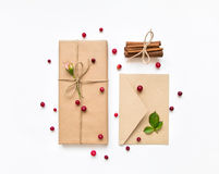 Gift box and envelope in eco paper on white background. Presents decorated with roses and berries. Holiday concept, top view, flat Stock Photo