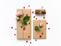 Gift box and envelope in eco paper on white background. Presents decorated with roses and berries. Holiday concept, top view, flat Stock Photos