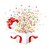 Gift Box Exploding. Confetti exploding from white gift surprise box with red bow Royalty Free Stock Photography