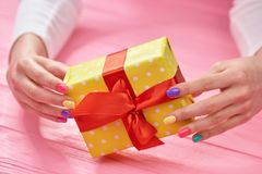 Gift box in female manicured hands. Stock Photos