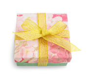 Gift box with festive floral prints and golden ribbon bow Stock Images