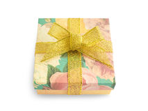 Gift box with festive floral prints and golden ribbon bow Stock Image
