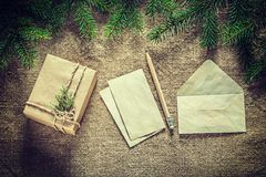 Gift box fir tree branch paper envelope pencil on sacking surfac. E Royalty Free Stock Images