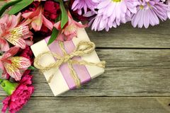 Gift box with flower border on wood Royalty Free Stock Photography