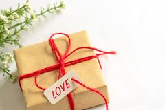 Gift box and flower, paper tag LOVE texting and copy space Royalty Free Stock Photography
