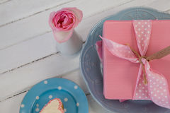 Gift box, flower vase and cookie on wooden surface Royalty Free Stock Image