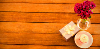 Gift box and flower vase with cupcake in plate on wooden plank Royalty Free Stock Photo