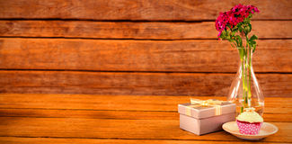 Gift box and flower vase with cupcake in plate on wooden plank Royalty Free Stock Photos