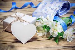 Gift box, flowers, card, ribbon and tie on wooden table Stock Photo