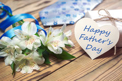 Gift box, flowers, card, ribbon and tie on wooden table Royalty Free Stock Images