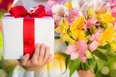 Gift box and flowers in hands Stock Photos