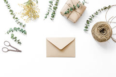 Gift box with flowers on white background top view space for text. Gift box with flowers an envelope for holiday on white table background top view space for Stock Photos
