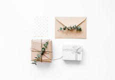 Gift box with flowers on white background top view space for text. Gift box with flowers an envelope for holiday on white table background top view space for Royalty Free Stock Image