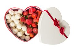 Gift box in the form of a heart on the Valentine`s Day is isolated on white background. Box in the form of a heart with. Strawberries and sweets. Sweet gift is Royalty Free Stock Photography