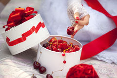 Gift box with fresh berries - cherry, raspberry, red currant, strawberry and hand of girl in lace mitts. Gift box with fresh berries - cherry, raspberry, red Royalty Free Stock Photo