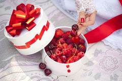 Gift box with fresh berries - cherry, raspberry, red currant, strawberry and hand of girl in lace mitts. Gift box with fresh berries - cherry, raspberry, red Stock Image