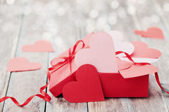 Gift box full of hearts on wooden background for Saint Valentines Day royalty free stock image