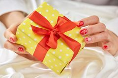 Gift box in gentle female hands. Royalty Free Stock Photos