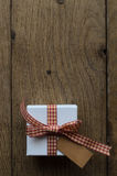 Gift Box with Gingham Ribbon and Blank Label on Wood Stock Image