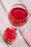Gift box and glass of pink wine Royalty Free Stock Photo
