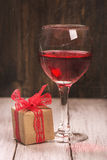 Gift box and glass of pink wine Royalty Free Stock Images