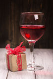 Gift box and glass of pink wine Royalty Free Stock Photography