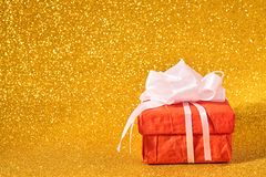 Gift box on gold background stock photos