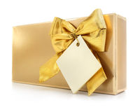 Gift box with gold bow and blank label Royalty Free Stock Image