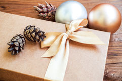 Gift box with gold bow with christmas balls and cone spruce on w Stock Photo