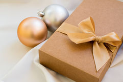 Gift box with gold bow and with christmas balls Royalty Free Stock Photo