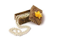Gift with necklace. Gift box with gold bow, which contains an elegant pearl necklace Stock Photo