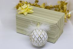 Gift box with a gold bow and white ball on a light background Royalty Free Stock Photography