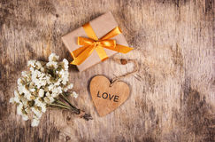 A gift box with a gold bow, white flowers and a wooden heart. A small present with a gold ribbon on a wooden background. Stock Photos