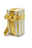 Gift box in gold duo tone with golden satin ribbon Royalty Free Stock Photos