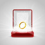 Gift box and gold ring in radiance Stock Images