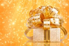 Gift box in gold wrapping paper Stock Images