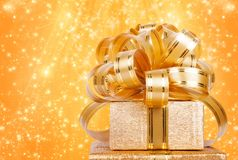 Gift box in gold wrapping paper Royalty Free Stock Image