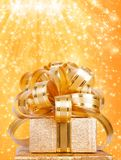 Gift box in gold wrapping paper Stock Photos