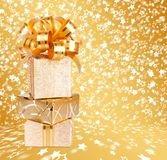 Gift box in gold wrapping paper on a beautiful  background Royalty Free Stock Photo