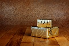 Gift box in gold wrapping paper with ribbon Royalty Free Stock Image