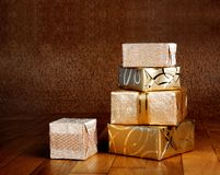 Gift box in gold wrapping paper with ribbon Royalty Free Stock Photography