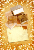 Gift box in gold wrapping paper on vintage cardboard background Royalty Free Stock Images