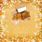 Gift box in gold wrapping paper on vintage cardboard Stock Images