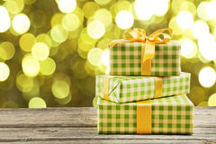 Gift box with golden bow on the grey wooden background Royalty Free Stock Images