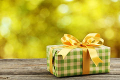 Gift box with golden bow on a grey wooden background Stock Photo