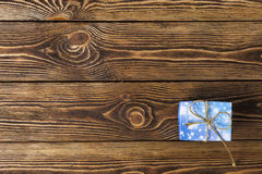 Gift box with golden bow on wooden table. Top view Stock Images