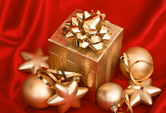 Gift box with golden christmas balls on red silk Royalty Free Stock Image